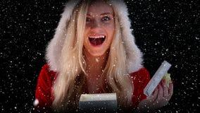 Video sammansättning med fallande snö över flicka i gåva för santas dräktinnehav arkivfilmer