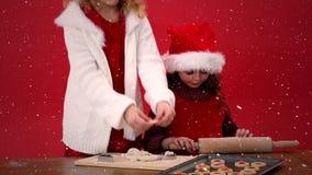 Video sammansättning med fallande snö över skrivbordet med ungar som förbereder kakor stock video