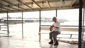 Video Senior Asian man riding a ferry boat to cross Chaopraya river in morning sun stock video
