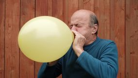 Mature man blowing a balloon. Video of senior caucasian man blowing a balloon until it explodes stock video footage