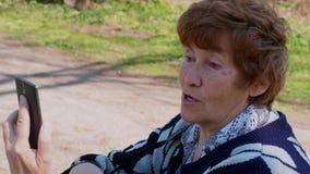 Video senior della donna che chiama tramite app mobile, ridente all'aperto archivi video