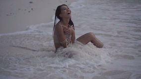 Video of smiling girl sitting on the beach and playing with wave splash in slow motion. Asian beautiful happy woman in crochet bikini sitting on the beach by stock footage