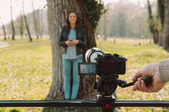 Video shooting at the park. Video camera and operator hand on foreground and female model standing in the background Stock Images