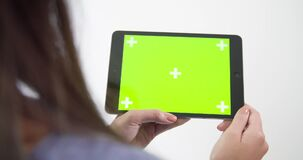 A shot of a young woman using an Ipad with green screen. Video of a shot of a young woman using an Ipad with green screen stock footage