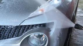 The video shows the washing machine. A powerful water pressure with foam is directed in the area of headlights, hood, water flows down, new technologies stock video footage