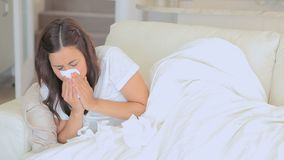 Video of sick woman sneezing and watching tv stock video footage