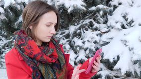 This video is about Side view portrait of an excited woman using a smart mobile phone in the park in winter. Slow motion stock video footage
