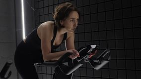 This video is about Side view of pretty attractive young woman enjoying her workout on exercise bike. Pretty girl cycling workout stock video footage