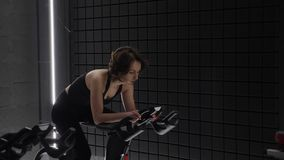 This video is about Side view of pretty attractive young woman enjoying her workout on exercise bike. Pretty girl cycling workout.  stock footage