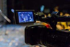 Video skytte av händelsen Camcorder med LCD-skärm 2 män på etapp framme av mikrofoner på en grå skärmbakgrund fotografering för bildbyråer