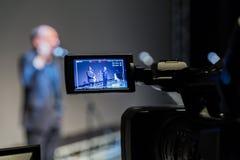 Video skytte av händelsen Camcorder med LCD-skärm 2 män på etapp framme av mikrofoner på en grå skärmbakgrund arkivfoton