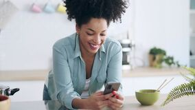 Smiling young woman sending messages with her mobile phone while drinking a cup of coffee in the kitchen at home.