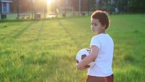 Video stående av fotbollsspelarepojken med bollen i parkera lager videofilmer