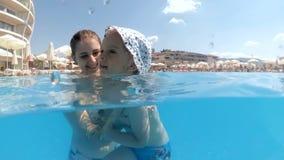 Video subacqueo del movimento lento della giovane donna sorridente con nuoto del ragazzo del bambino nello stagno all'aperto alla archivi video