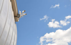 Video surveillance. Two surveillance cameras on the background of the cloudy sky stock photo