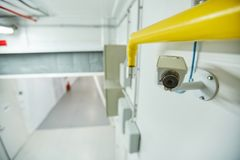 Video surveillance in corridor. Small modern video surveillance camera on upper part of wall under yellow tube in corridor, copy space royalty free stock photos