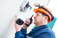 Technician worker installing video surveillance camera on wall. Video surveillance. Technician worker installing wall camera with screwdriver Royalty Free Stock Photos