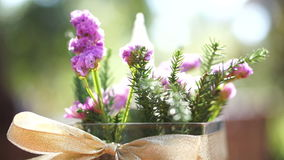 Video Table decorated with glass vase flowers on ribbon. Beautiful morning sun light stock footage