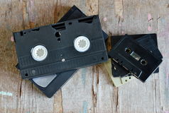 Video tape and cassette tape on wood board Royalty Free Stock Photography