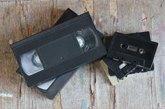 Video tape and cassette tape on wood board Royalty Free Stock Photo