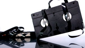 Video tape falling and bouncing on white background Stock Photos