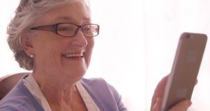 Video telefono cellulare rivolgentesi della donna senior stock footage