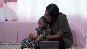 Video tilt up of Mother is teaching daughter to know different colors, African American families in a pink bedroom.