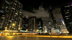 Chicago Skyscrapers at Night with Cars Crossing the City. Video timelapse of Chicago downtown skyscrapers with cars driving at full speed on its streets stock video footage