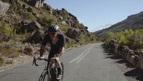 Cyclist doing uphill ride on mountain roads stock video footage