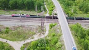Video train with cars passing under the bridge with the road. Video from the drone. Video train with cars passing under the bridge with the road. Video from the stock video