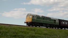 Train passing by a green field in Norwich. Video of train passing by a green field in Norwich stock footage