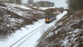 Train travels through the snowy countryside in England. Video of train travels through the snowy countryside in England stock footage