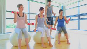 Video of a trainer teaching his class. On exercise ball lifting weights stock footage