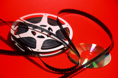 Video Transfer. 16mm movie reel and a dvd on a red background Stock Image