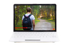 Video travel blog concept - man walking in forest in video on la. Video travel blog concept - man with backpack walking in forest in video on laptop screen Stock Images