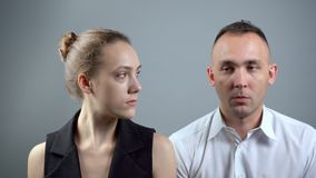 Video of two boring people on grey background. Video of man and woman sitting near on grey background stock footage