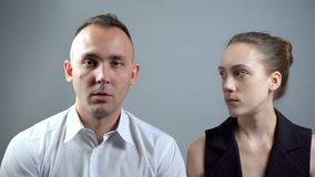 Video of two boring people on grey background. Video of man and woman sitting near on grey background stock video footage