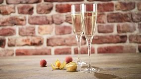 Video of two flutes of champagne on the wooden table with the brick background, selective focus stock video footage