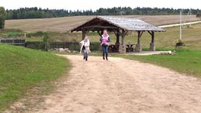 Two happy girls running along the road in the village. Video of two happy girls running along the road in the village stock footage