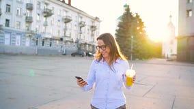 4 in 1 video Uomo e donna che parlano sullo smartphone e sul succo bevente che camminano giù la via, movimento lento stock footage