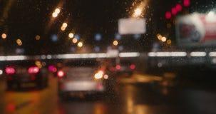 Video vago delle automobili che si muovono lento verso il limite nella notte piovosa stock footage