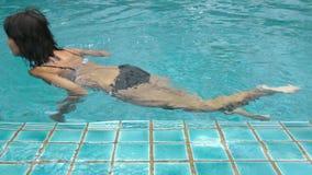 Video van een aantrekkelijke vrouw die in de pool zwemmen stock videobeelden
