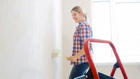 Video van mooie het glimlachen jonge vrouw het schilderen muren in haar huis met witte verf en rol stock video