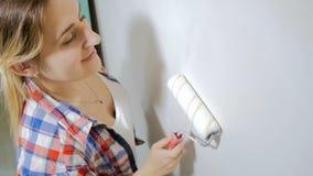 Video van mooie het glimlachen jonge vrouw het schilderen muren in haar huis met witte verf en rol stock footage