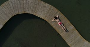Video van vrouw in zwempak die op de pijler zonnebaden Het vrouwelijke ontspannen op vakanties stock video