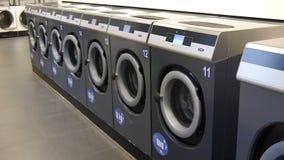 Video van zelfbedieningswasserij - muntstuk laundrywashing machines en kleurrijke wasserij stock footage