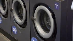 Video van zelfbedieningswasserij - muntstuk laundrywashing machines en kleurrijke wasserij Close-up stock footage