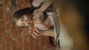 Video verticale Bella donna bionda che mangia e che beve nel ristorante, intervallo di pranzo video d archivio