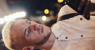 Video verticale Giovane uomo attraente facendo uso dello smartphone sulla via della città di notte Uomo facendo uso del telefono  video d archivio