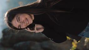 Video verticale Una giovane donna sta parlando sul telefono nella condizione sulla cima della roccia I viaggi turistici dentro stock footage